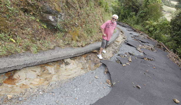 STRANDED: Bill Tito surveys the damage to his washed-out driveway after a deluge of rain in Akatarawa Valley overnight.