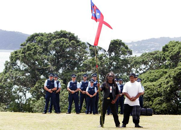 A local stands and waves his flag in front of a group of police on the Treaty grounds on Waitangi Day, Waitangi, Bay of Islands in 2009.