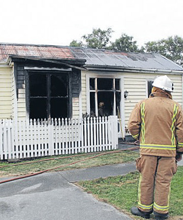 Mataura deputy fire chief Neville Phillips looks at the fire damage to a River St property.