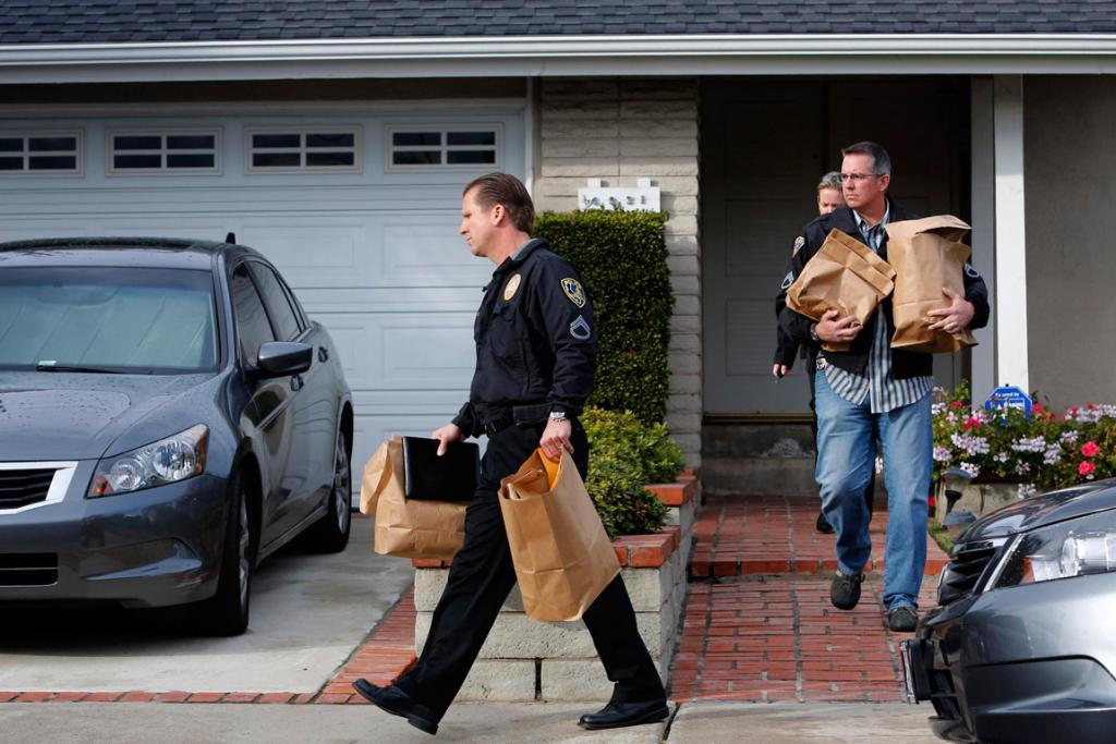 Investigators from Irvine and Riverside police carry out bags of evidence after serving a search warrant at the home of Christopher Dorner's mother in La Palma, California, on February 8 (local time).