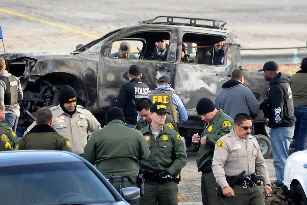 Law enforcement personnel gather in front the truck authorities have identified as belonging to ex-LAPD officer Christopher Dorner as it's towed after being discovered burning on a US Forestry Department road in the Bear Mountain Resort on February 7, 2013.