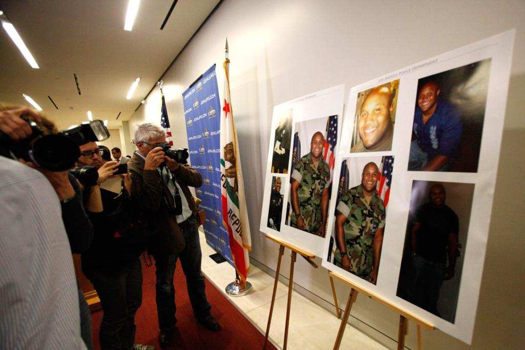 Members of the media take pictures of the photos of shooting suspect Christopher Jordan Dorner during a news conference at LAPD headquarters.