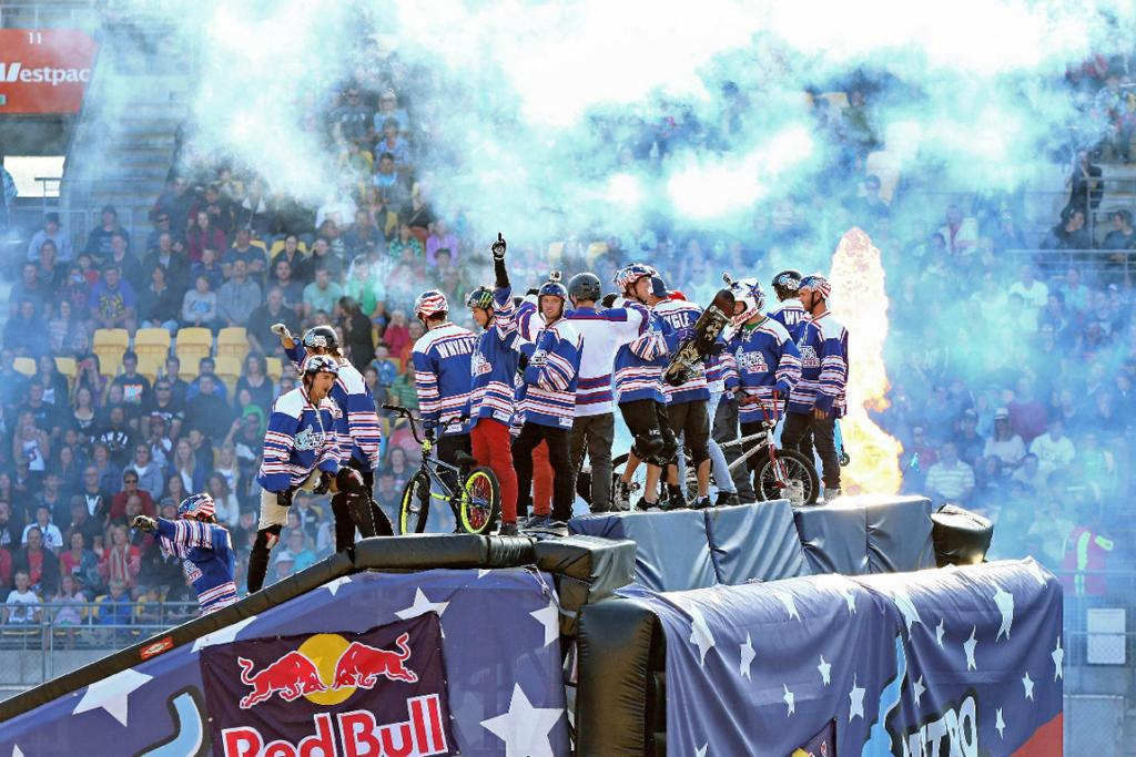 A group of BMXers and skaters show off to the crowd at the top of the ramp.