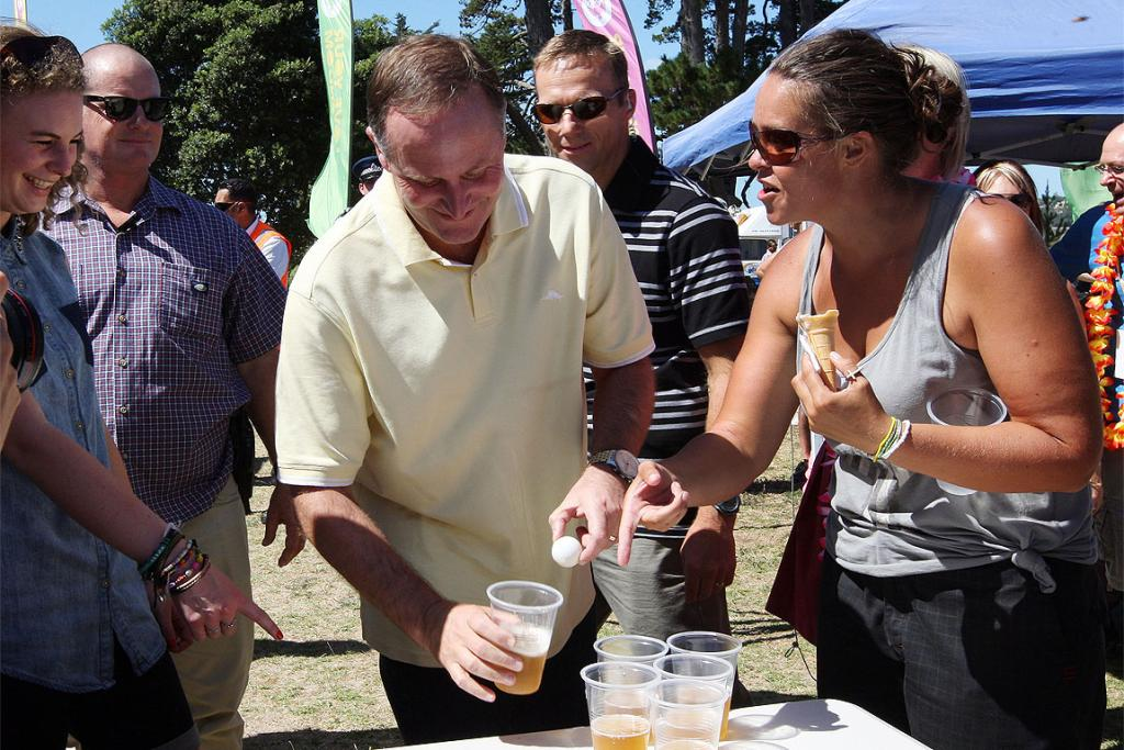 Prime Minister John Key gets a lesson in beer pong at the Big Gay Out in Auckland.
