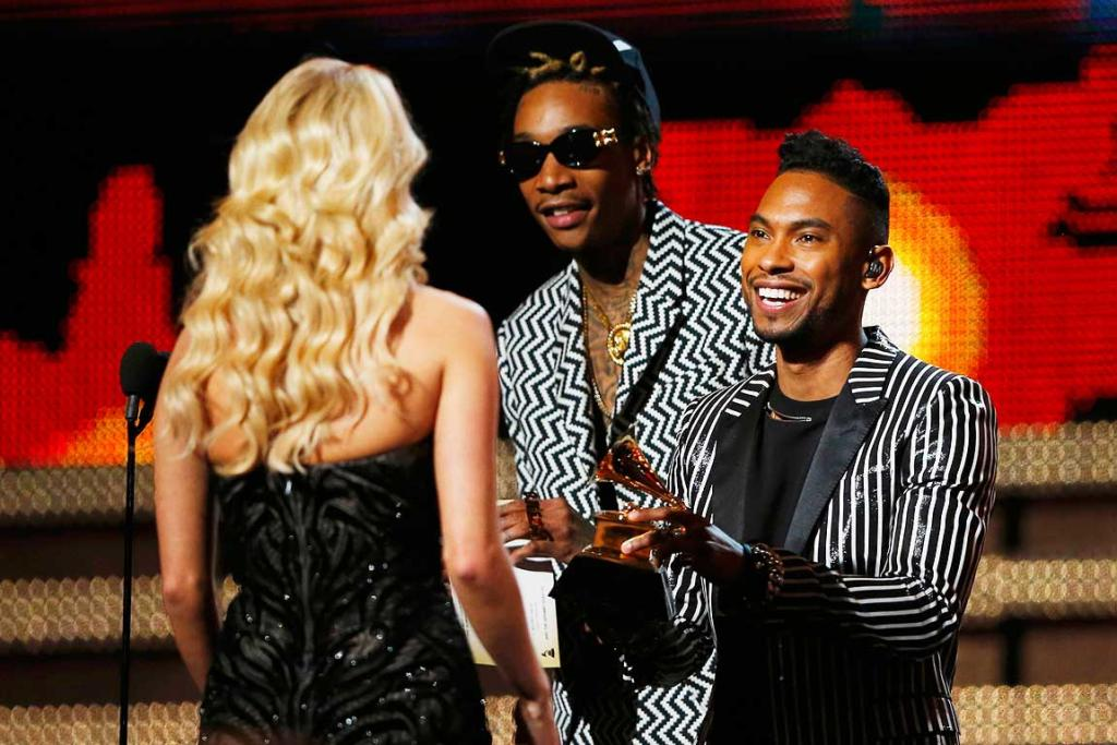 Carrie Underwood accepts the Grammy for best country solo performance for Blown Away from presenters Miguel (C) and Wiz Khalifa (R).