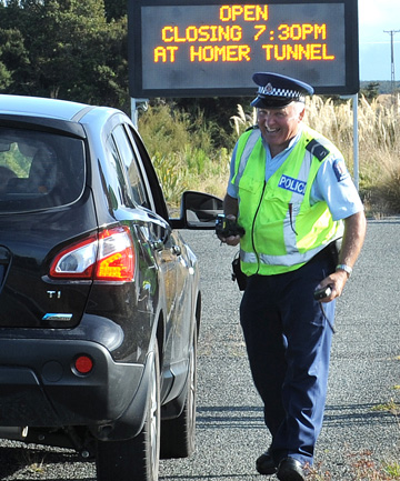 Senior constable Ray Stelvie stops a vehicle on the Milford Road, north of Te Anau, during a joint police and NZ Transport Agency operation targeting tourists.
