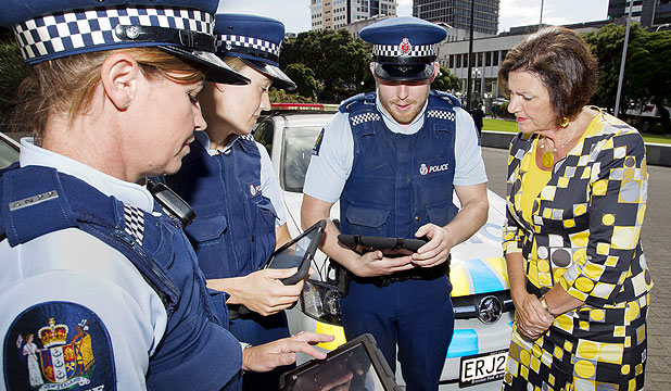 TECHED UP: Police Minister Ann Tolley talks with, from left, Detective Constable Andrea Quinn, Constable Harriet Murray and Detective Richard Gibson about their new iPhones and iPads.