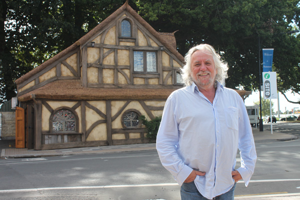 Academy Award winning art director Dan Hennah poses for a photo in front of the i-SITE Gatehouse he helped to design.