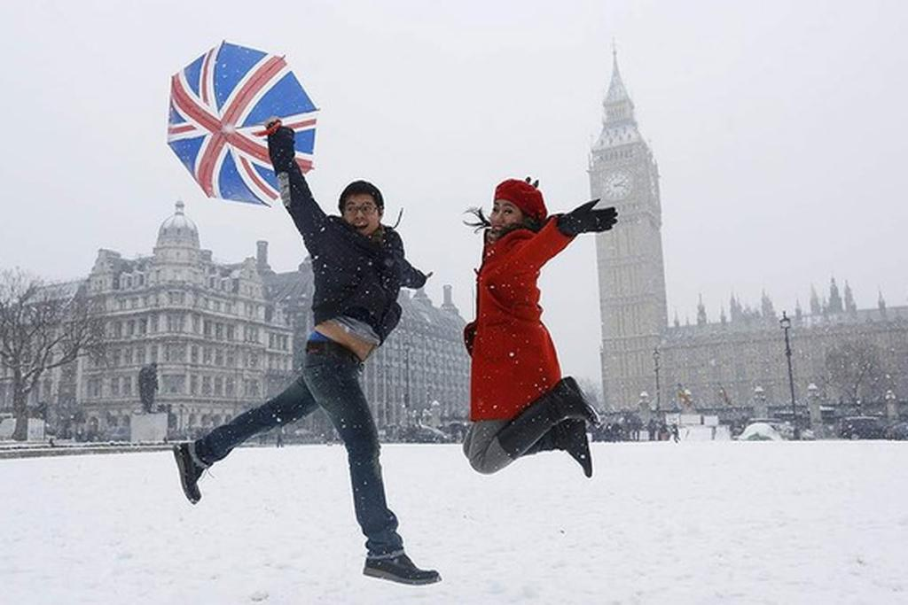 Tourists from Indonesia jump for a souvenir photograph in front of the Houses of Parliament during a snowfall in central London.