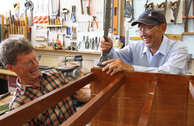 Team effort: Hamilton Community Men's Shed Trust chairman Dr Neil Bruce, left, and 79-year-old You Ben Ma restore a chest of draws.