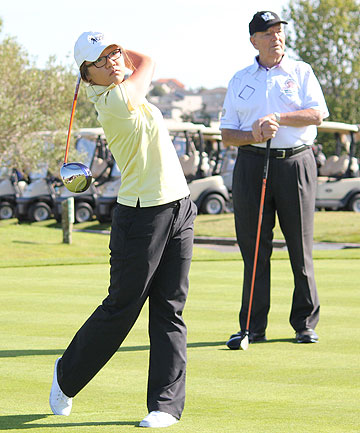 TOP CLUB: Lydia Ko drives in front of Sir David Levene at the Gulf Harbour Country Club.