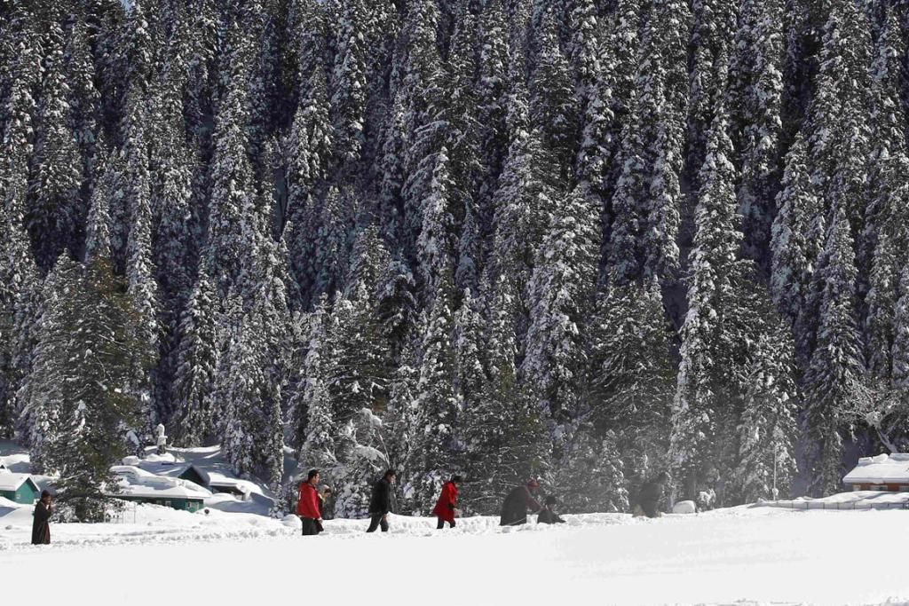 Tourists walk past snow-covered trees in Gulmarg, west of Srinagar, India.