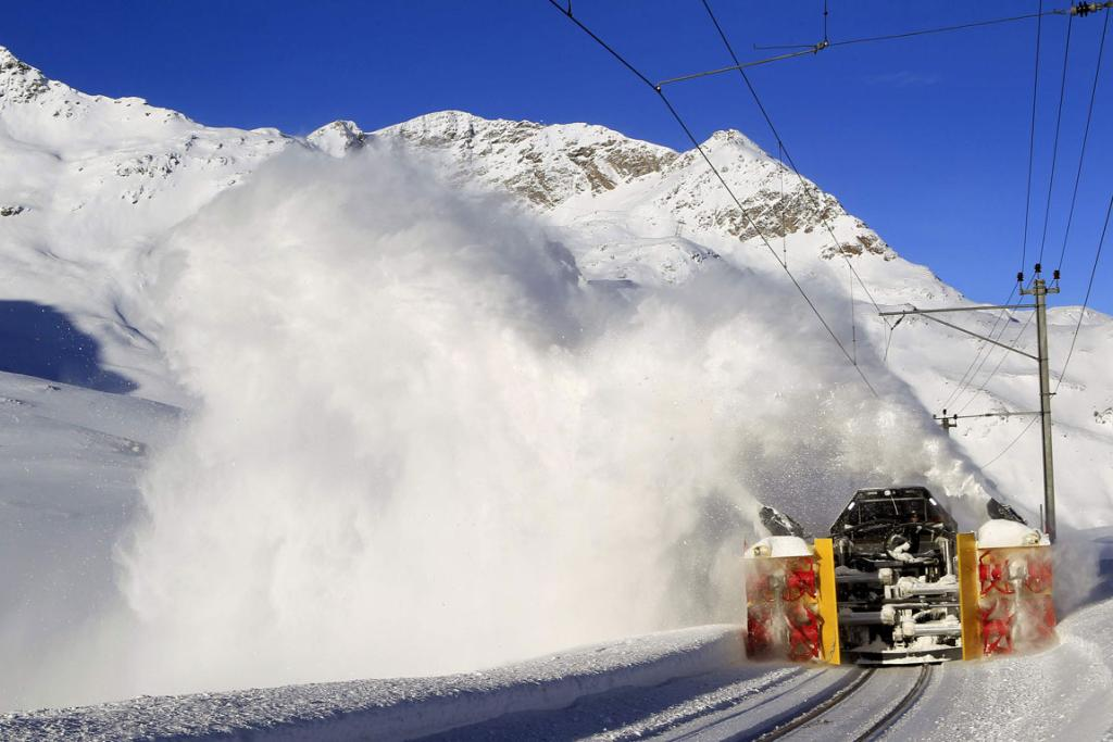 A railway worker steers a Zaugg snowblower along the tracks of the Rhaetische Bahn Bernina in southern Switzerland.