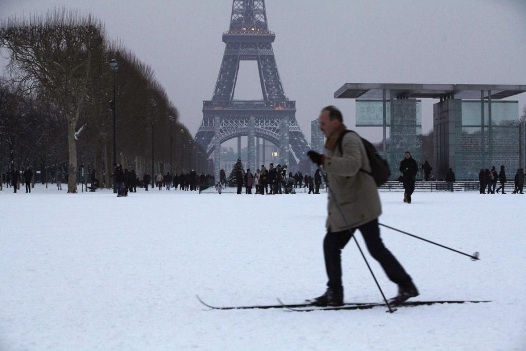 A local skis cross-country across the snow-covered Champs de Mars near the Eiffel Tower in Paris.