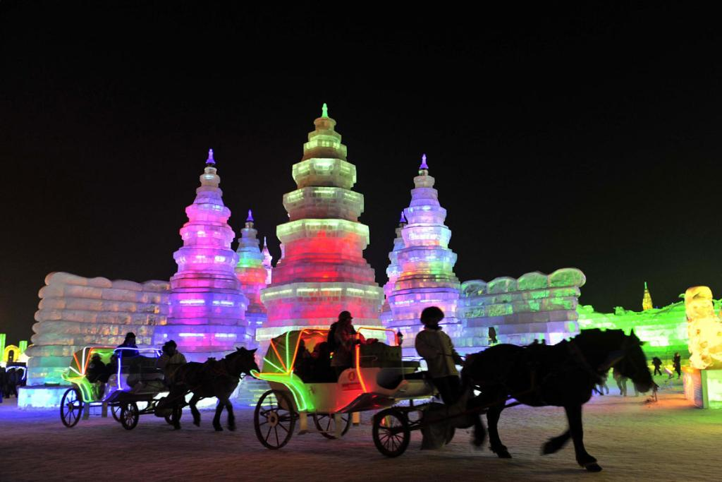 Horse carriages carrying tourists travel past ice sculptures during the Harbin International Ice and Snow World festival in Heilongjiang province, China.