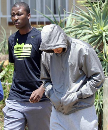"PODIUM TO JAIL CELL: South African ""Blade Runner"" Oscar Pistorius covers his face with a hood as he is escorted by police at a Pretoria police station."