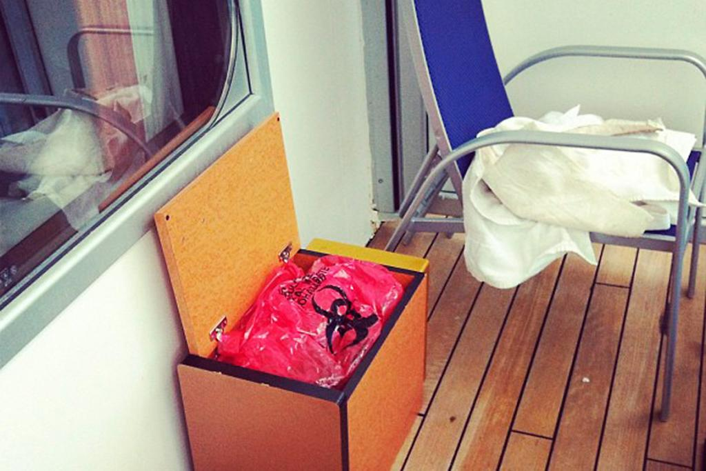 A photo by Jacob Combs of bag of human waste in a box on the outdoor deck of a room.