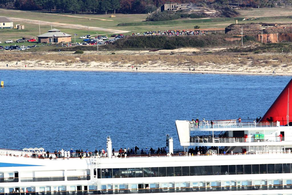 People watch on as the cruise ship is towed toward the port of Mobile, Alabama.