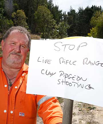 WARNING: John Hodge with the sign he placed at the gate when he was target shooting on his Ruby Bay property.