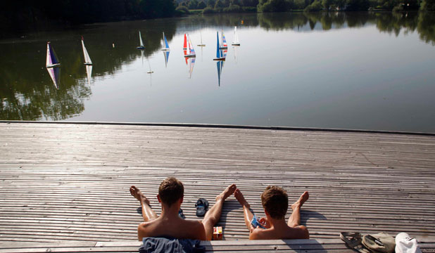 Boys admire model sailboats during a regatta at Koseze pond, Ljubljana.