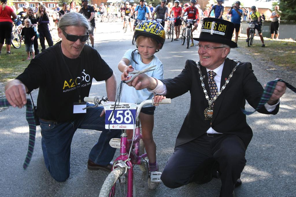 DEED DONE: Waitaki Mayor Alex Familton, right, cuts the ribbon with the youngest rider, Suzie Smith of Omarama, and Ohau Lodge owner and Alps 2 Ocean chairman Mike Neilson.
