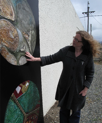 Riverton Community Arts Centre gallery co-ordinator Dianne Robinson examines the new mural by Dunedin-based painter Tony Tarasiewicz.