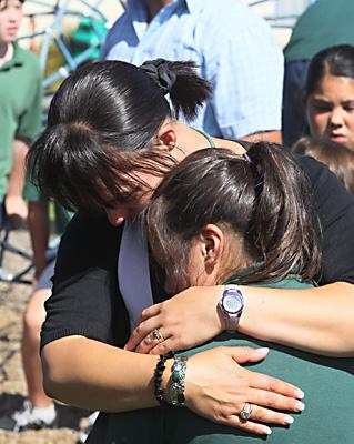 COMFORTED: Phillipstown School teacher Sunny West hugs one of her pupils after they were told the news their school will merge with Woolston School.