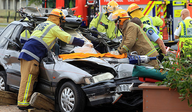 TRAPPED: Emergency services work to free a person from the wreckage of the  Honda.