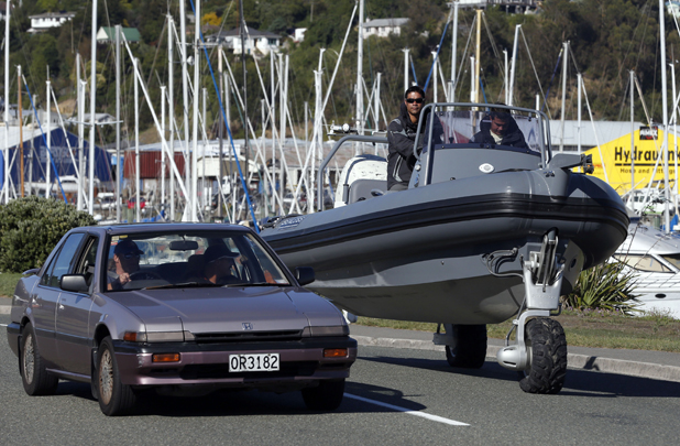 David McKee Wright, left and Warren Farr are past by a car as they drive to the launch ramp at the Nelson Marina before leaving Nelson for Westport during their circumnavigation of the South Island in the latest model Sealegs Amphibious marine craft.