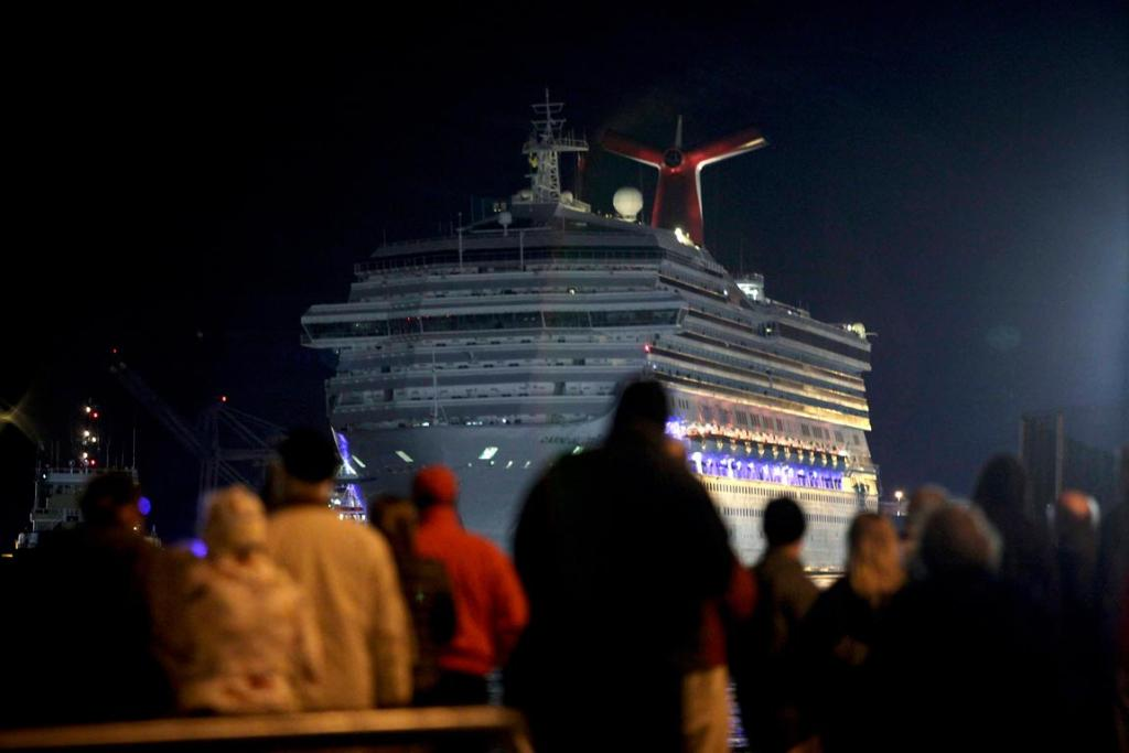The Carnival Triumph cruise ship is towed towards the dock as spectators watch at the port of Mobile, Alabama, on February 14.