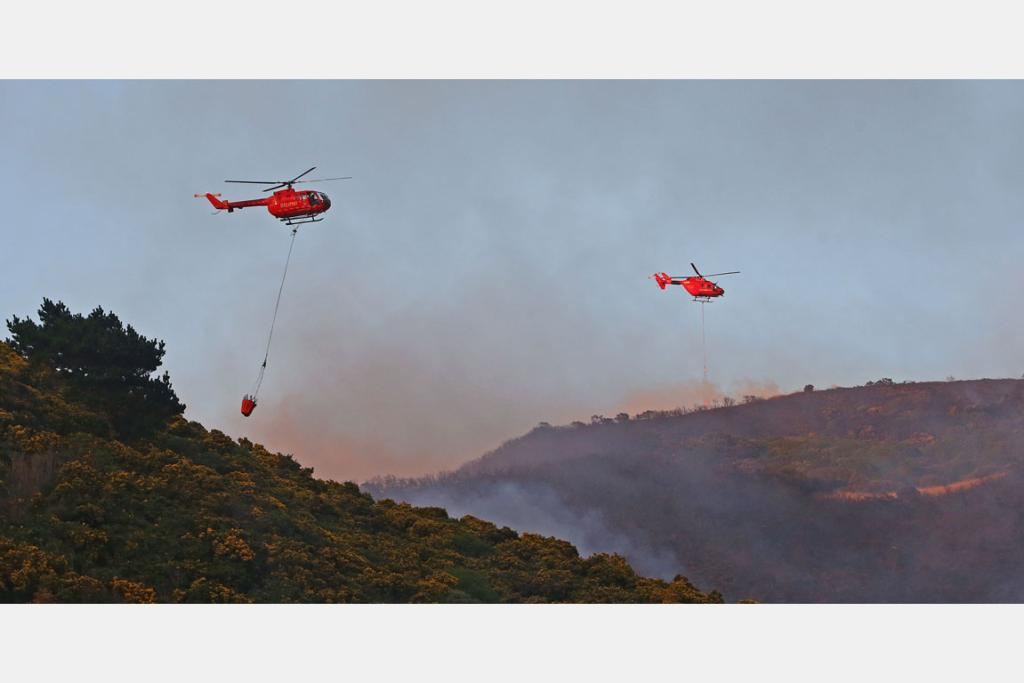 Helicopters carry monsoon buckets to help with the fire in Owhiro Bay, Wellington.