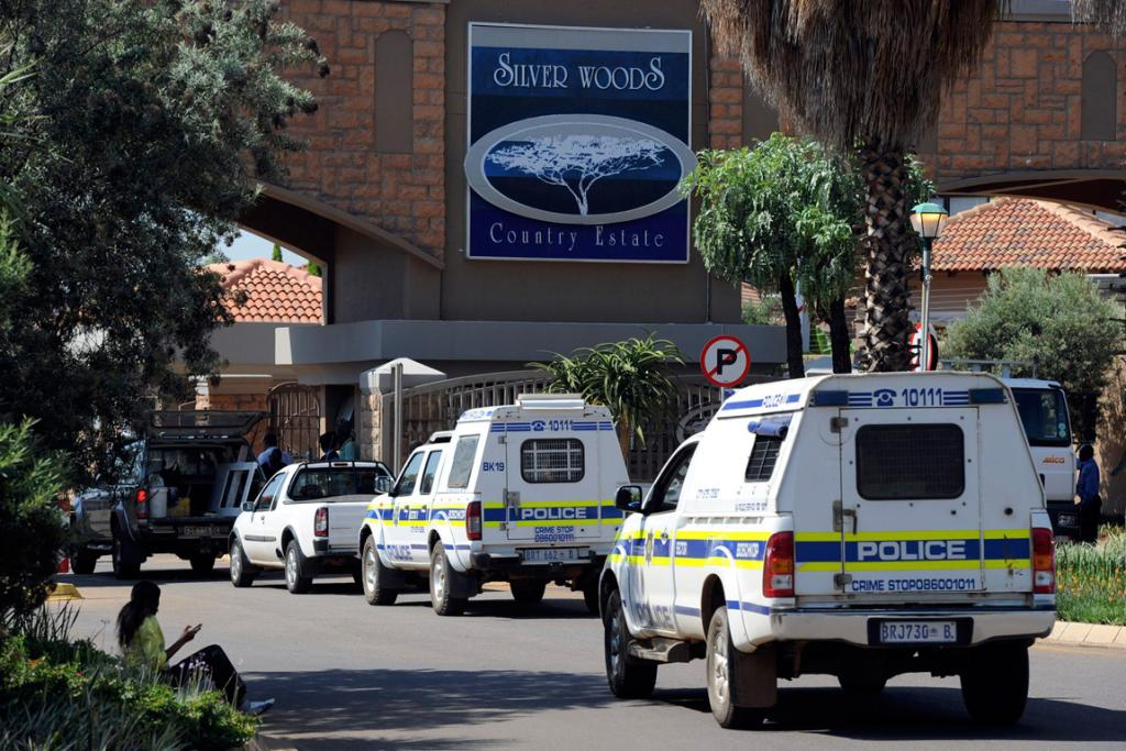 Police vehicles enter the private townhouse complex where Oscar Pistorius lives on the day of the murder.