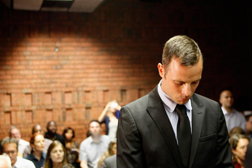 Oscar Pistorius stands in the dock during a break in court proceedings at the Pretoria Magistrates court, a day after he was charged with mudering his girlfriend Reeva Steenkamp.