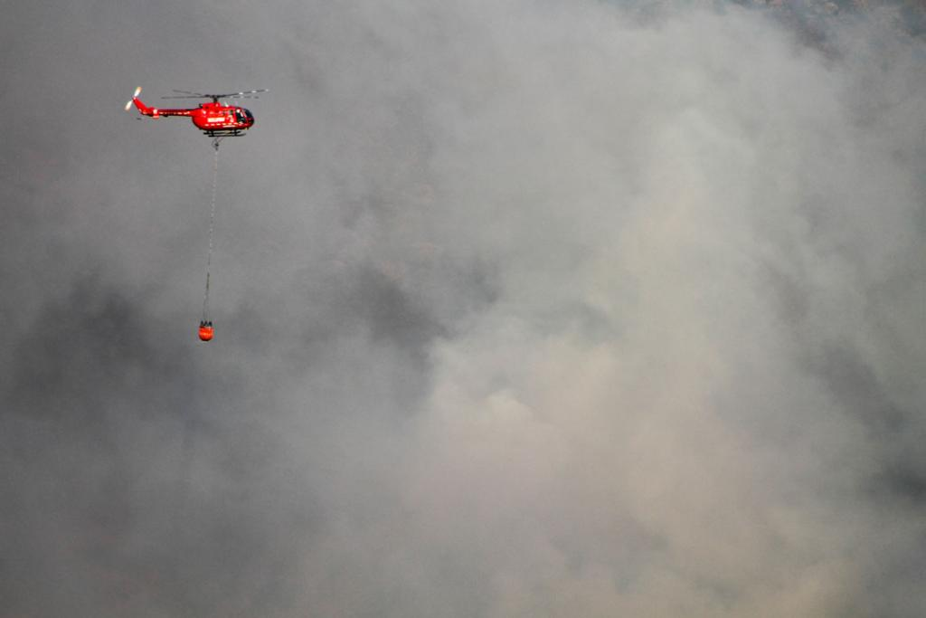 A helicopters armed with a monsoon bucket fights the fire.