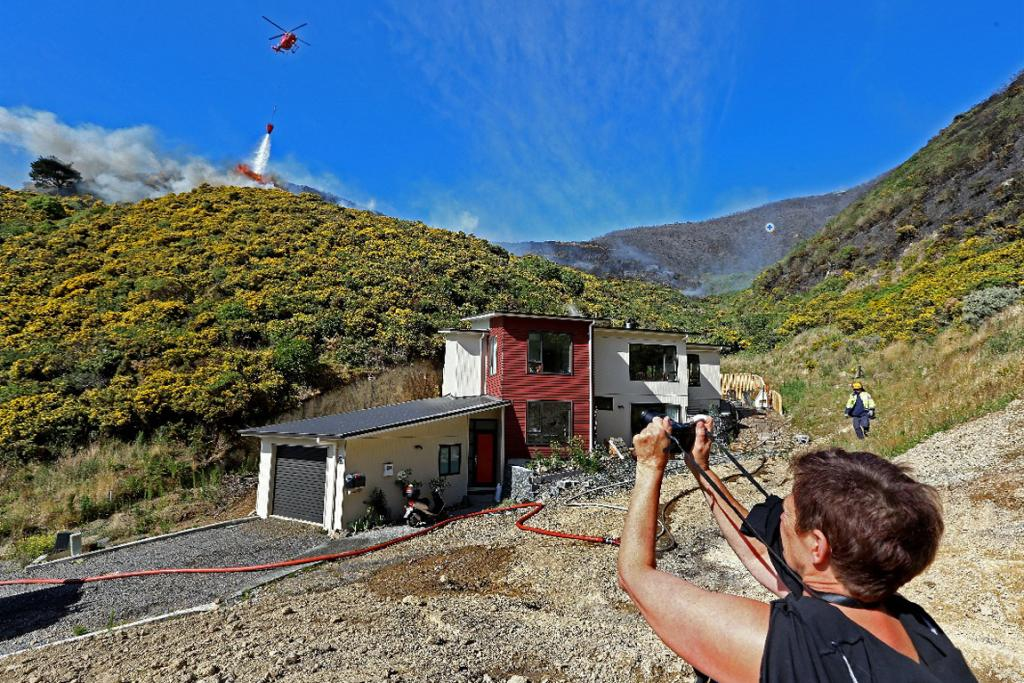 Rarangi Way resident Terri Shaw takes a photo of her house, threatened by flames Thursday morning.
