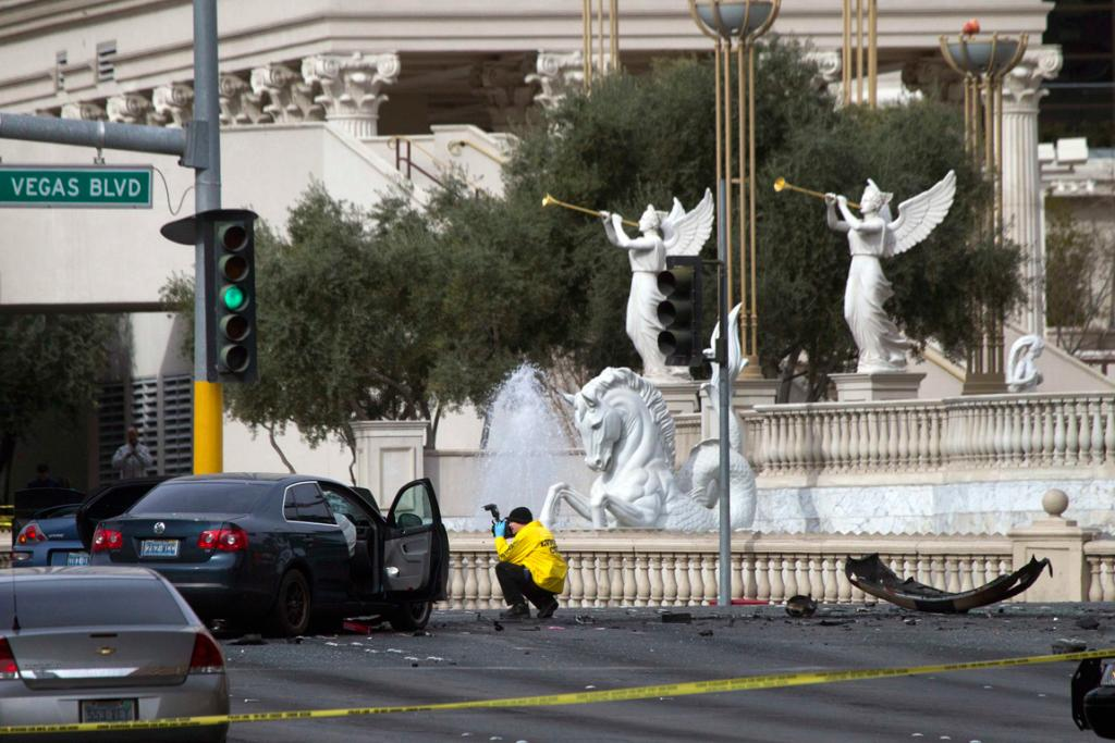 A crime scene analyst photographs a car in front of Caesars Palace after the shooting.