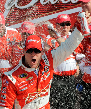 FROTHING FOR A RACE: Kevin Harvick celebrates with his Nascar race team after securing third place on the grid for the Daytona 500.