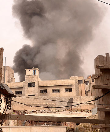 BATTLEGROUND: Smoke rises near Souk al-Zahraoui, in the old city of Aleppo, as forces loyal to Syria's President Bashar al-Assad are deployed against the Free Syrian Army.