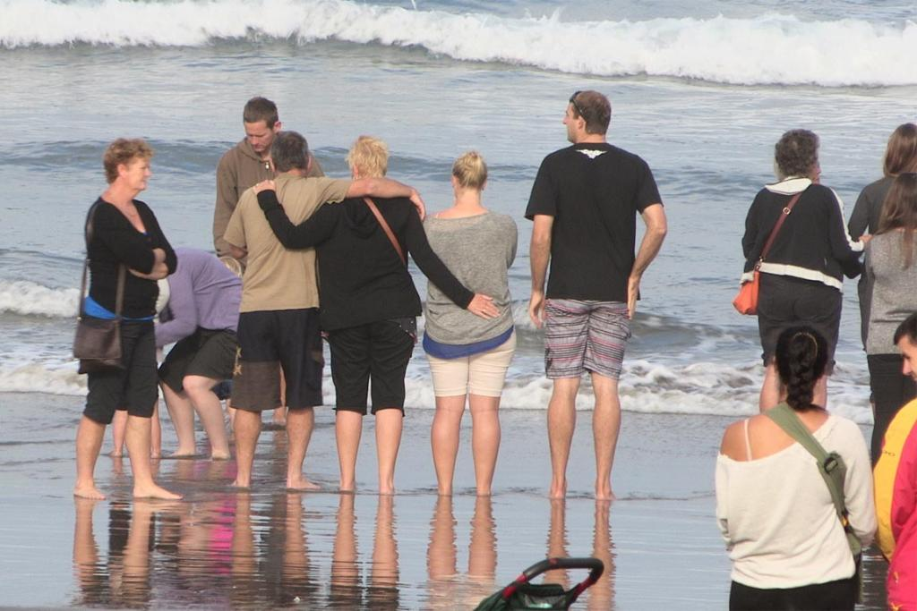 Family and friends of Adam Strange embrace during a ceremony at Muriwai Beach, a day after he died in a shark attack.