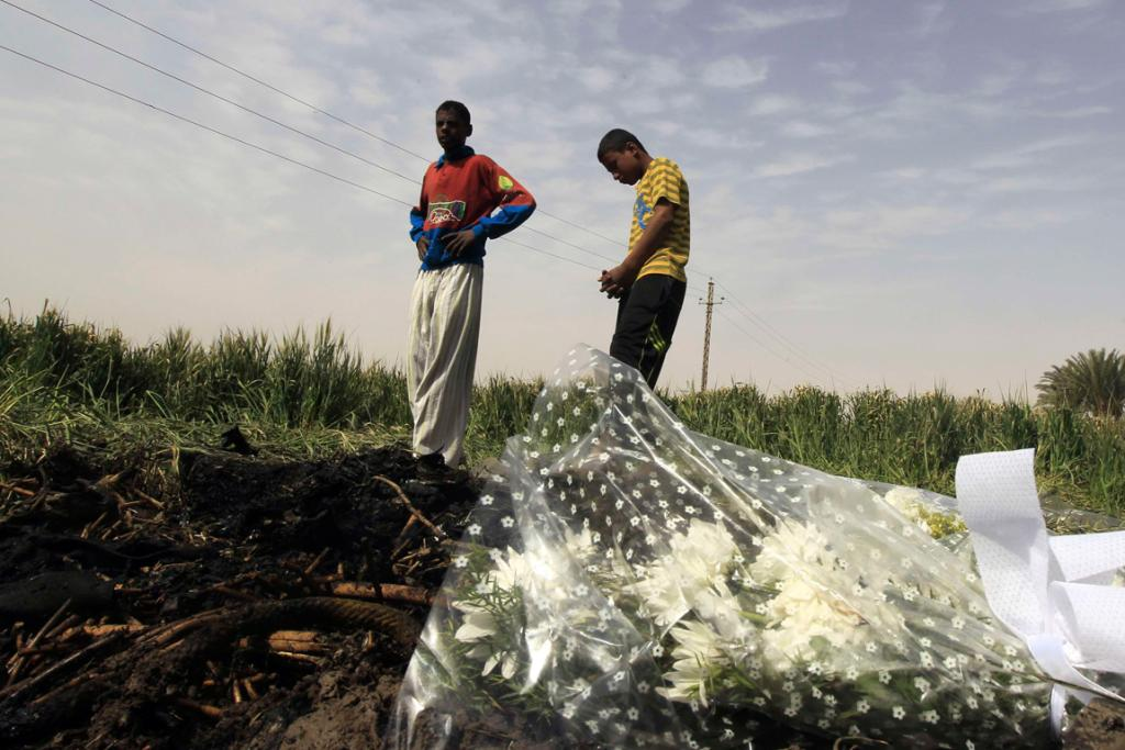 Residents walk near the wreckage of a hot air balloon that crashed in Luxor, killing 19.