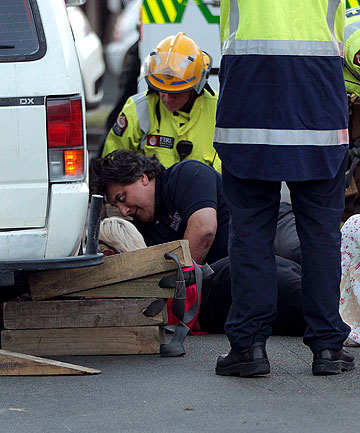 TRAPPED: Emergency services workers free a boy who was stuck under a van at a pedestrian crossing on the corner of Broadway and The Square in Palmerston North.