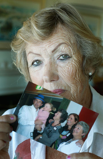 Kay Cresswell with a photo of Mr Strange and his family, including his mother at right.