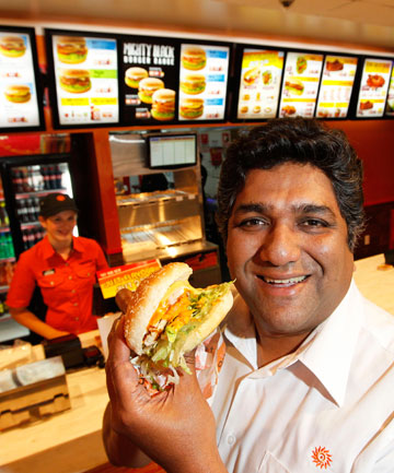 Oporto chief executive Bhushan Arolkar tastes a Bondi Burger at the new Courtenay Place store on Thursday.