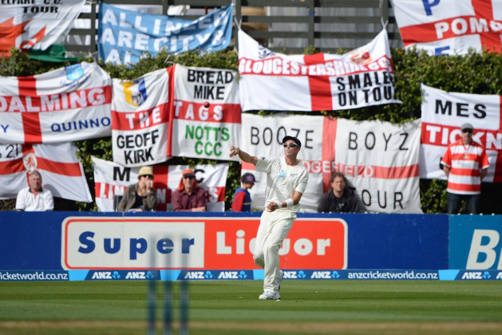 Tim Southee in the outfield with dozens of English flags waving in the background.