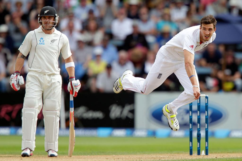 Steven Finn of England bowls while Brendon McCullum looks on.