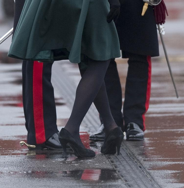 Britain's Prince William supports his wife Catherine, Duchess of Cambridge as she pulls her heel from a grate during a visit on St Patrick's Day to Mons Barracks in Aldershot, southern England.