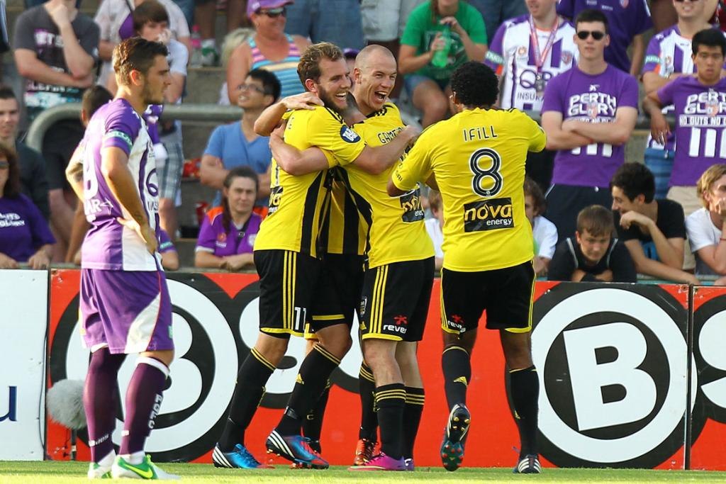 Wellington Phoenix players celebrate after scoring against Perth Glory.