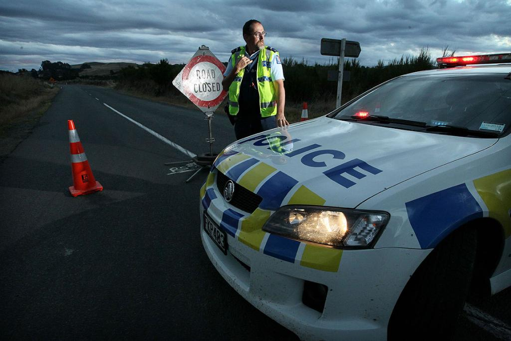 Senior Constable Steve Maddrin guards the road near the scene of the fatal shooting.