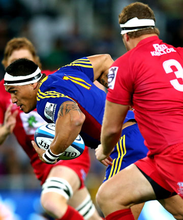 PUSHING ON: Highlanders wing Hosea Gear splits the Queenslad Reds defence at Forsyth Barr Stadium in Dunedin tonight.