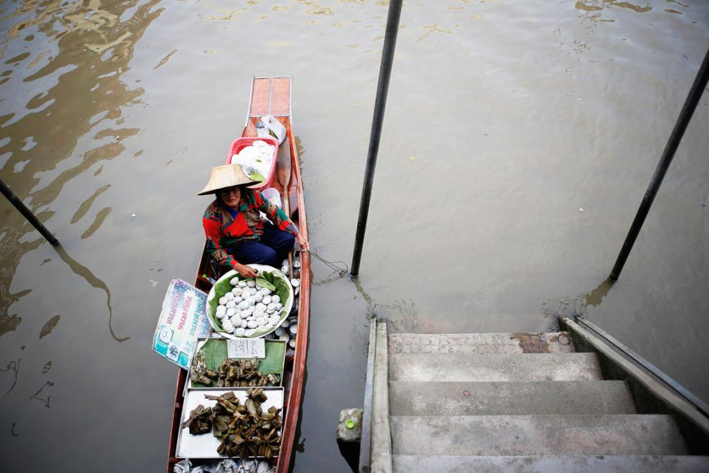 A vendor offers food from her small boat.